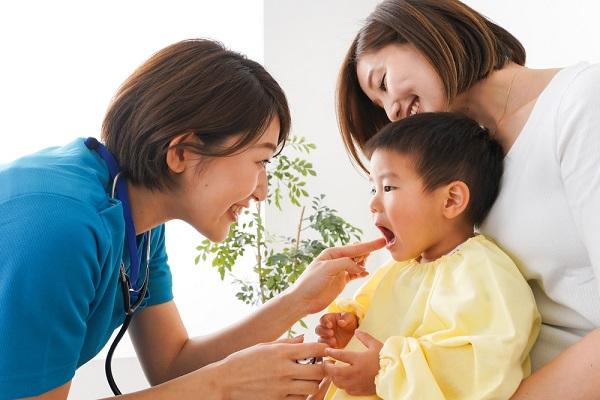 子どもを診察する看護師