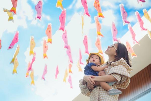 こいのぼりを眺める2歳児の子どもの写真