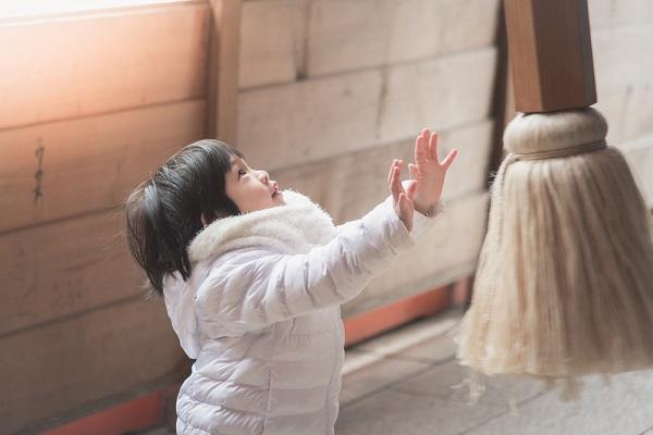 寺の鐘を鳴らす子どもの写真