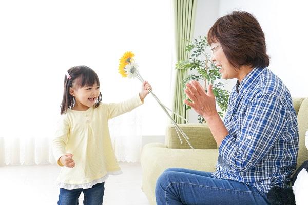 おばあちゃんに花を渡す女の子