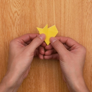 クリスマスの切り絵 折り紙を一回折りの状態にして、右側を折り、左側を重ねる工程