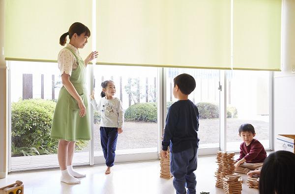 ロールスクリーンを操作する松村先生と室内で遊ぶ子どもたち