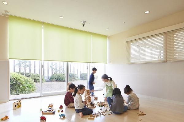 室内で子どもの保育をする先生と遊ぶ子どもたち