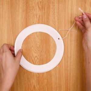 紙皿の端に穴を開けて紐を通して結ぶ