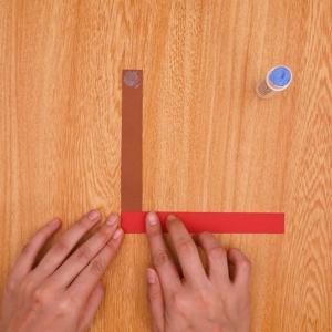 茶色の画用紙の両端にのりをつけて赤色の画用紙と貼り合わせる工程