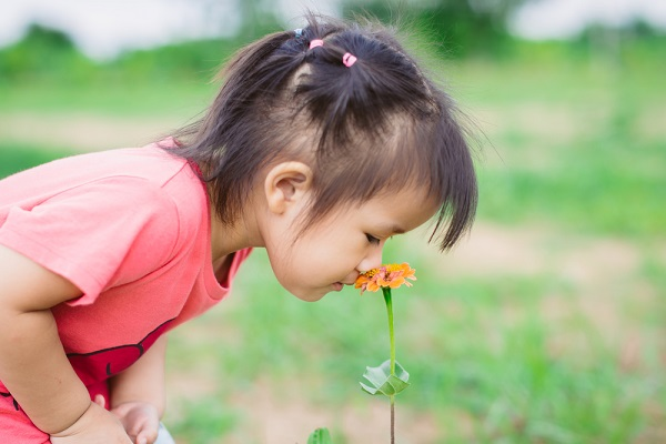 花の香りを楽しむ子ども