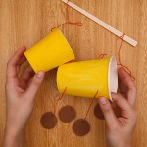 キリで穴をあけて、毛糸を2穴に通して割り箸の両端に結ぶ