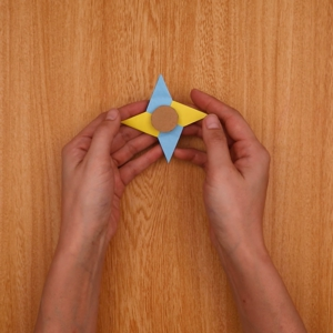 ダンボールに接着剤をつけて綿棒を差し込み、折り紙をもう1つのダンボールで挟む