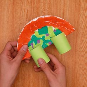装飾した紙皿にパーツをはさみます。