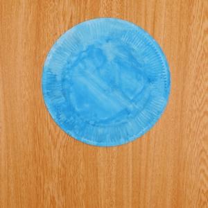 紙皿に絵の具を塗って乾かす工程