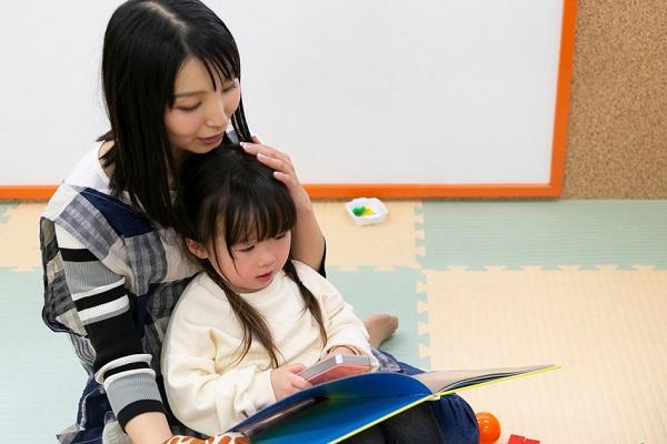 読み聞かせをする保育者と絵本見る子ども
