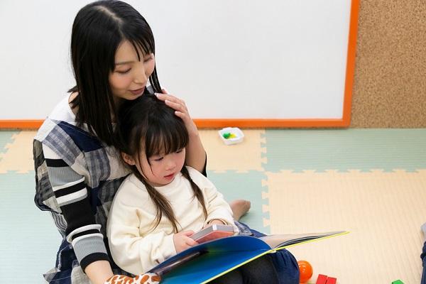 絵本を読む保育士と子ども