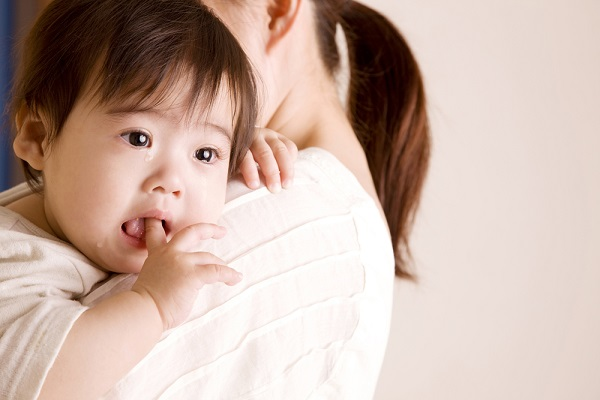 女性に抱っこされている子どもが泣いている写真