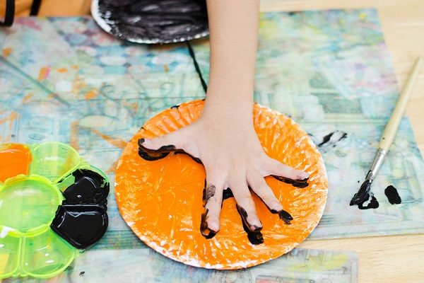 紙皿に手形スタンプをする様子