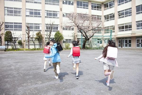 校庭を走る小学生の写真