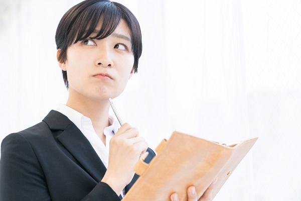 スーツを着て考え事をしている女性の写真