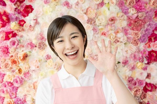 笑顔で手を振っている保育士の写真