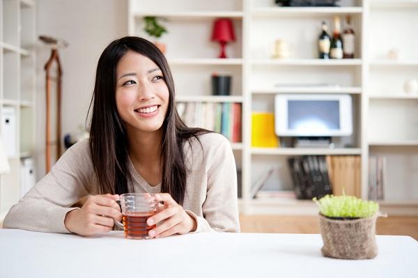 自室でお茶を飲んでいる女性の写真