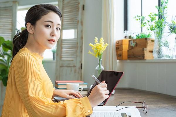 PCとノートで勉強する女性の写真