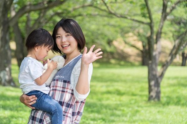 子どもを抱いて手を振る保育士の写真