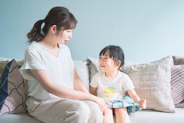 笑顔で会話する保育士さんと女の子の写真