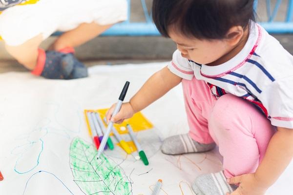 製作遊びをする2歳児の子どもの写真