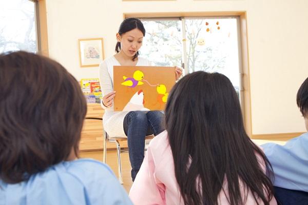子どもたちに紙芝居を読み聞かせる先生