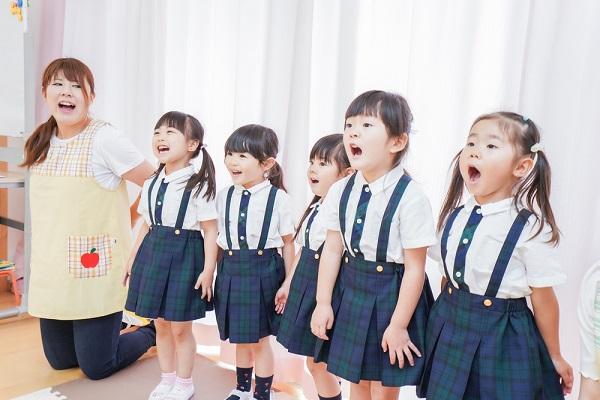 保育園で歌っている子どもの写真