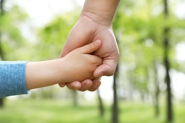 手をつなぐ親子の写真