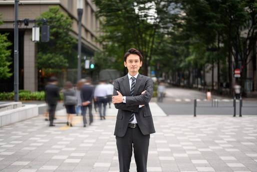 都会に立つ会社員の男性
