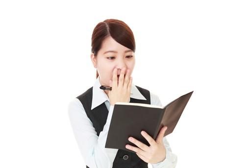 手帳を見て驚く女性