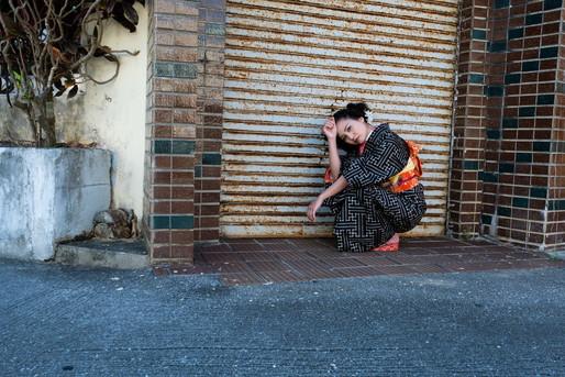 道端でうずくまる和服の女性