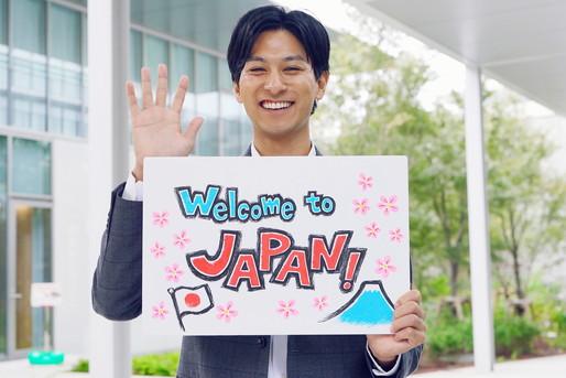 ウェルカム日本のボードを掲げる男性