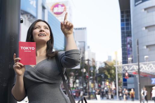 東京ガイドブックを持って歩く女性