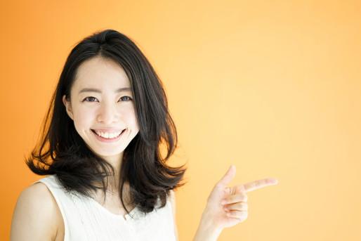 指をさす笑顔の女性