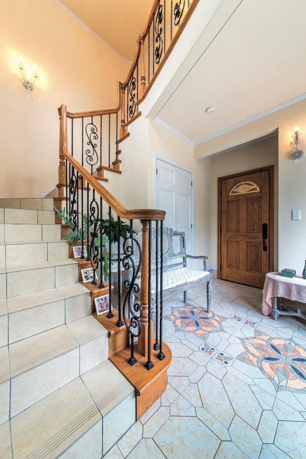 スペイン製の床タイルが広がるエントランスから優美に立ち上がるサーキュラー階段。木製の手摺りとアイアンバラスターを採用し、重厚感のある仕上がりに