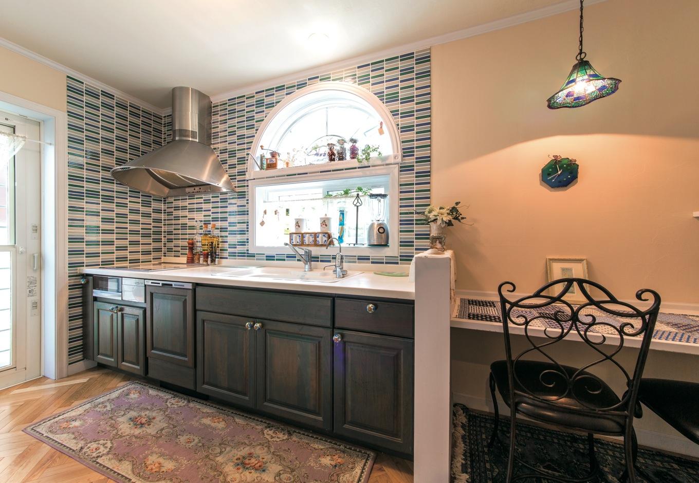 ハーフサークルウィンドーからやわらかな光が降り注ぐキッチン。スモーキーなオリーブ色のキッチンパネルもお気に入り。隣接する家事コーナーで絵ハガキを書くことも