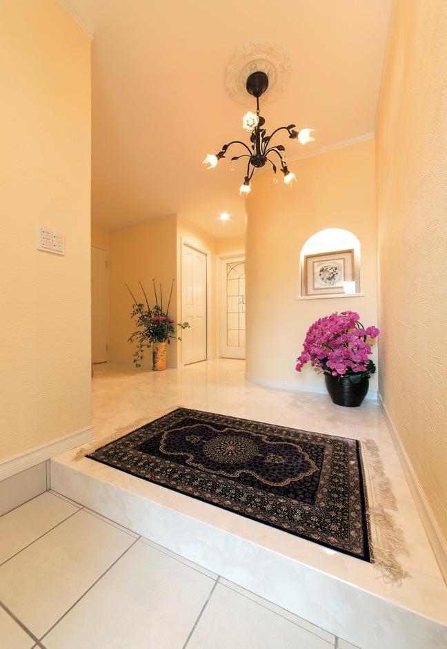 大理石調の床と珪藻土の塗り壁を使用した玄関。Rの壁にやさしさを感じる