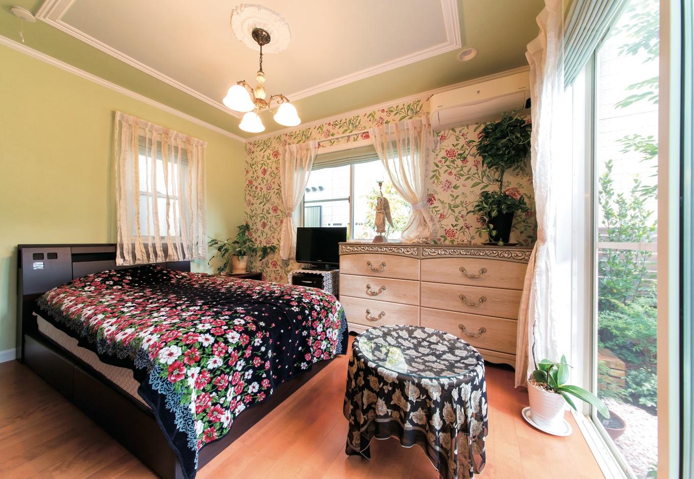中庭をのぞむ寝室。英国サンダーセンの壁紙が空間のアクセントに。家具、照明、カーテンのコーディネートも絶妙