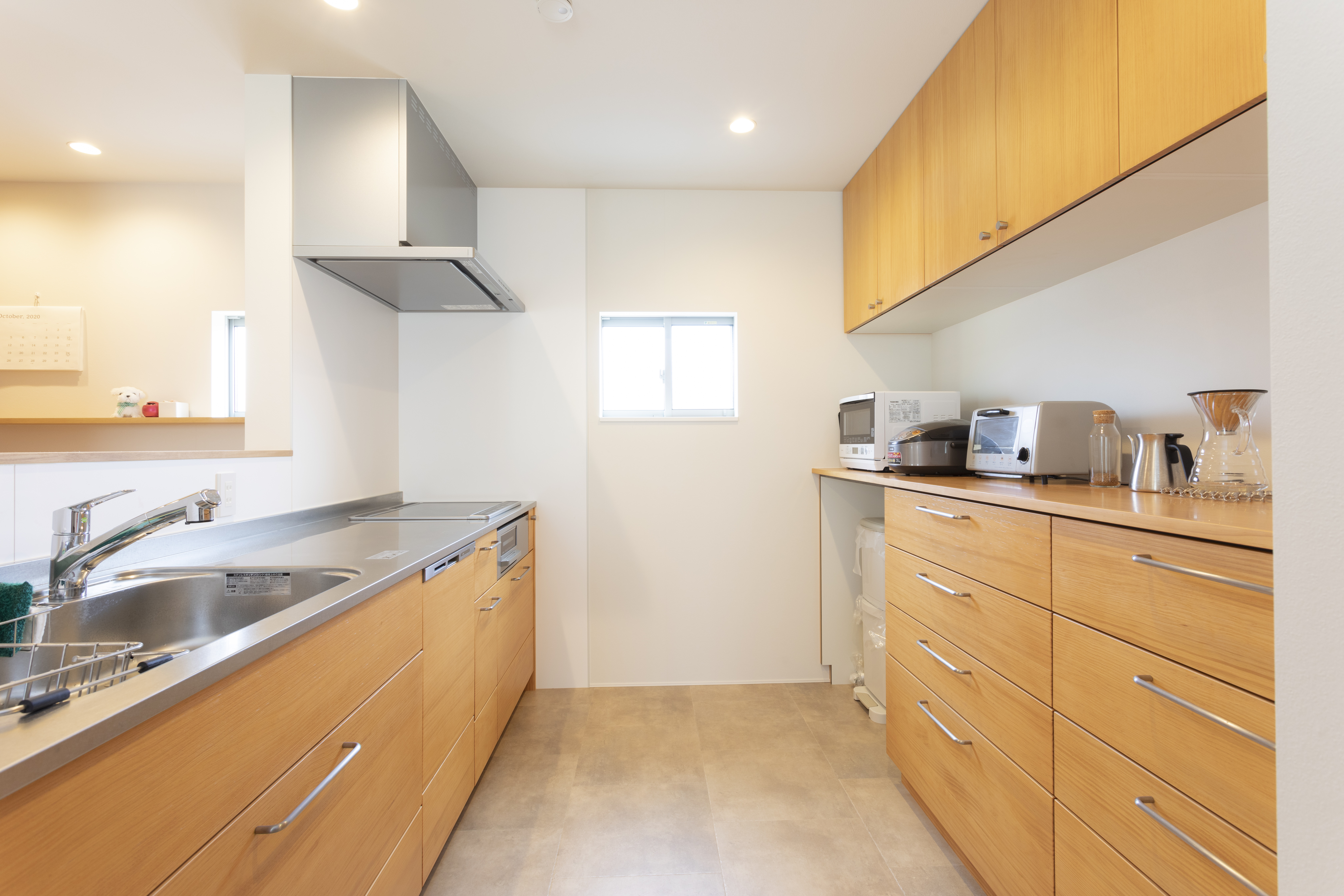 アトリエプラス【収納力、自然素材、間取り】キッチンとカップボードの間を広めに取ったことで、家族みんなで協力しながら広々と使える空間に。掃除がしやすいよう、キッチン部分の床だけ材質を変えている。