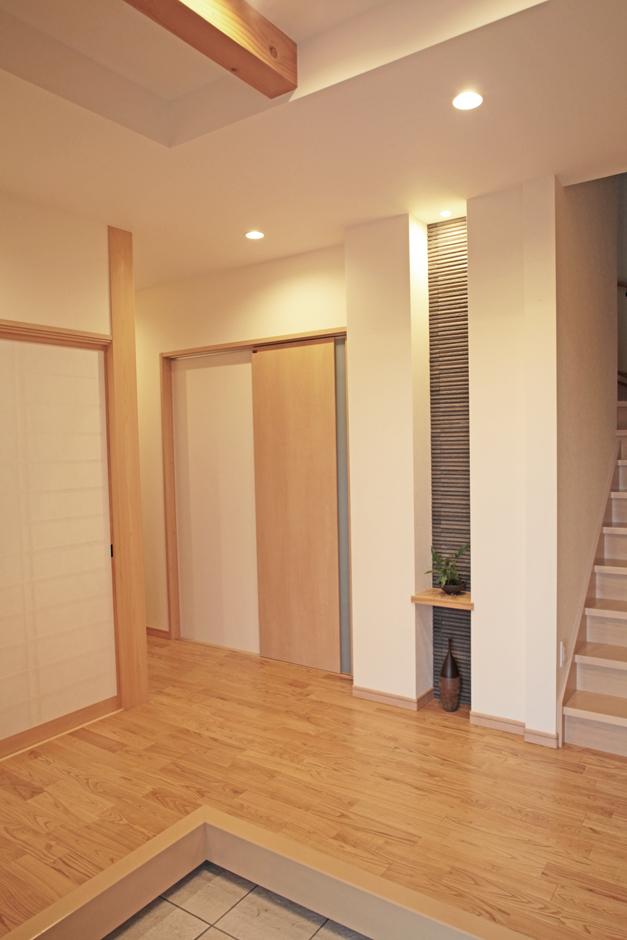 AS STYLE (アズ スタイル)【子育て、二世帯住宅、インテリア】広々としたゆとりのある玄関。正面に縦長のニッチを設け、玄関外の外壁と同じタイルをニッチにも使い、一体感を持たせたデザインに