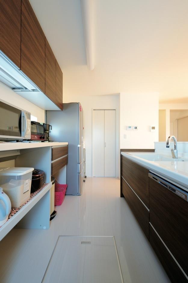 絆家  (きずなや)【1000万円台、デザイン住宅、省エネ】ダークブラウンのキッチンがナチュラルカラーの部屋に映える。鏡面仕上げの床は汚れにくくお手入れもラク