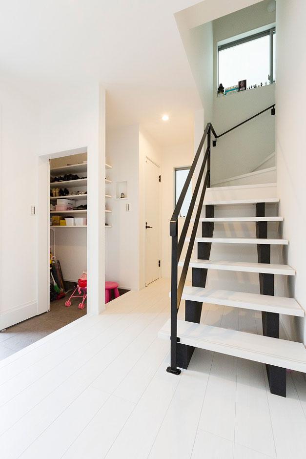建築システム(狭小住宅専門店)【デザイン住宅、間取り、インテリア】家族の帰宅後は、シューズクロークで靴を整理整頓してから上がる動線になっている。スライディング引戸で目隠しもでき、急な来客があっても安心だ。階段はスケルトンにすることで、ホールにより一層の開放感がもたらされた