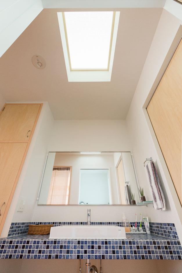 爽やかなモザイクタイル張りの洗面。トップライトの光で一日中明るい脱衣・洗面室となった