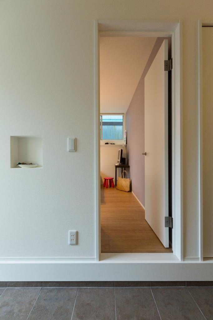さりげないニッチがアクセントの玄関横の寝室入口。寝室壁紙はシンプルな淡いラベンダー色でリラックス空間。実際は見えないクローゼットの中の壁紙がストライプ。奥様は見えない所で遊んでみたとのこと