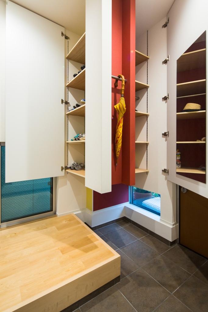 玄関横のシュークローゼットと傘などの収納スペースは壁紙で遊び心を演出し、鏡も設置して狭い空間を有効に活用