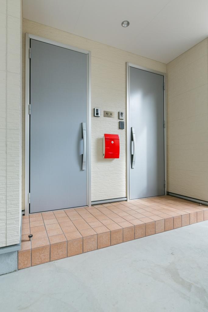 建築システム(狭小住宅専門店)【二世帯住宅、狭小住宅、ガレージ】二世帯のため、玄関ドアも2つ設置。真っ赤なポストが目をひく。都市型シンプルデザイン