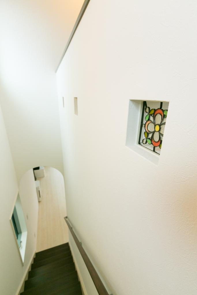 建築システム(狭小住宅専門店)【二世帯住宅、狭小住宅、ガレージ】階段室には、ステンドグラスを埋め込んでアクセントに。塗壁調の壁面がプロバンスの雰囲気を醸し出している