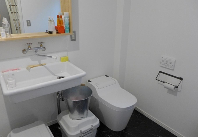 学校の理科室スタイルの洗面で蛇口も2ハンドル。バケツもブリキ製で、トイレは最新型のタンクレス・アラウーノというギャップが楽しい
