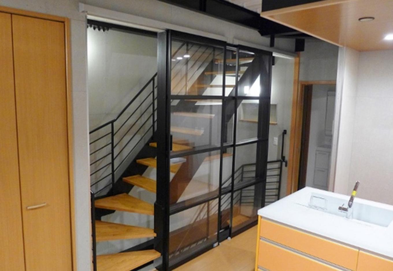 リビングに造ったスケルトン型の階段はスライド式のアクリル製パネルで仕切り視線に広がりをもたせた